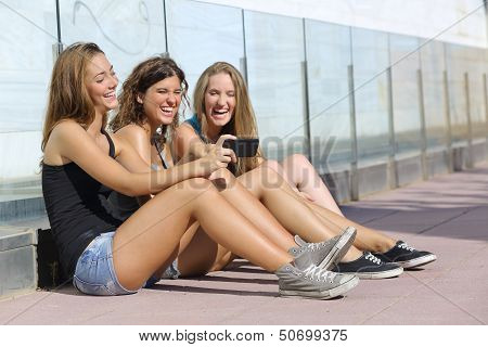 Group Of Three Teenager Girls Laughing While Watching The Smart Phone