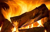 stock photo of combustion  - Logs of wood burning bright in a wood fire