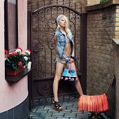 foto of roller-derby  - Sexy Young pretty blonde woman standing with roller skaters in jeans shirts in the city - JPG