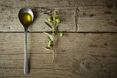 stock photo of olive branch  - Green olive branch and a spoon full of oil on the wooden table - JPG