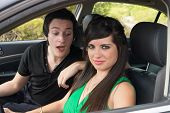 stock photo of clevage  - Cheeky guy peeping into the female drivers clevage - JPG