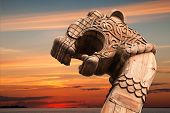 stock photo of historical ship  - Carved wooden dragon on the bow of Viking ship above evening cloudy sky - JPG