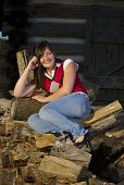 Teenager Relaxing On Woodpile By Cabin poster