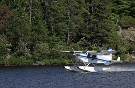 picture of float-plane  - A float plane taking off from a lake in Muskoka Ontario Canada - JPG
