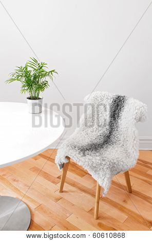 Chair Covered With Sheepskin, And Plant On A White Table