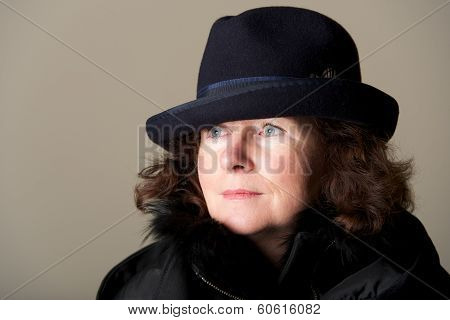 Brunette staring in black trilby and coat