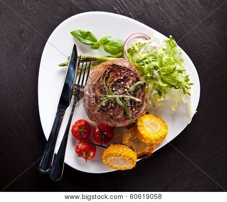 Piece of red meat steak with vegetable, herbs and spices, served on black stone surface. Shot from top view