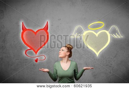 Pretty young woman standing and deciding between the angel and the devil heart