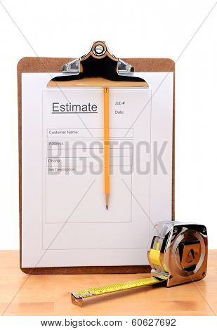 Closeup of a Contractors estimate form with a pencil and tape measure on a wooden table. Vertical on a white background.