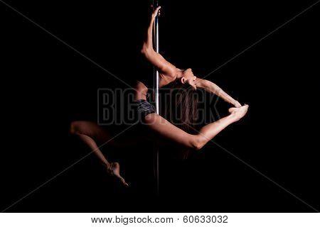 Sexy pole dancer in dark setting