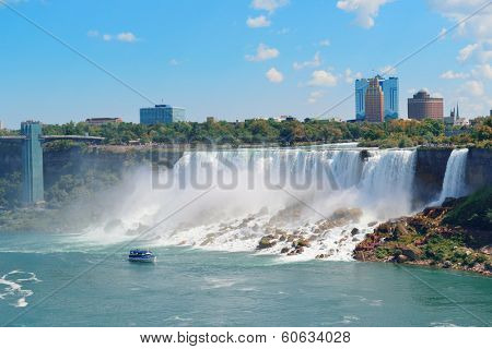 Niagara Falls closeup in the day over river with rocks and boat