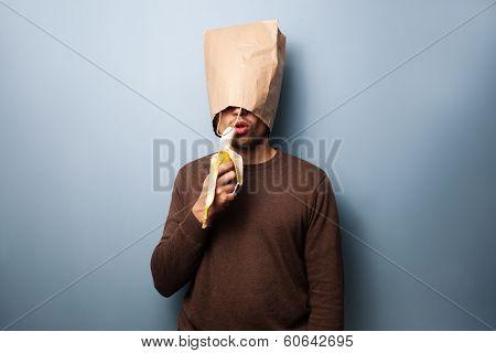 Young Man With Bag Over Head Eating Banana