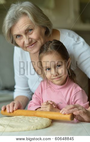 Little girl with grandmother kneading dough