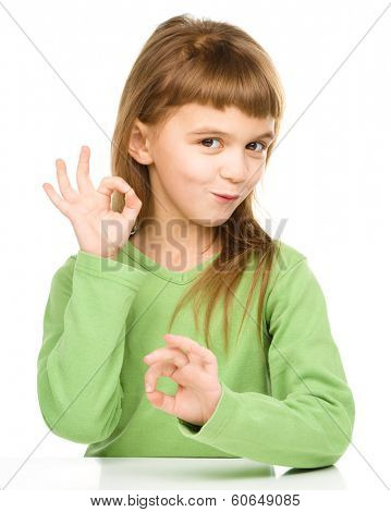 Happy little girl is showing OK sign using both hands, isolated over white