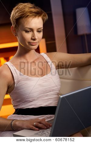 Smiling young woman using laptop computer at home, working in cosy room.