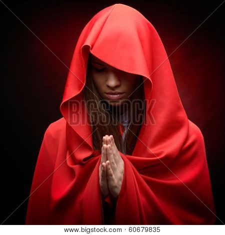 beautiful woman with red cloak in studio praying