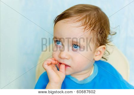 Sad child puts his finger in his mouth looking away