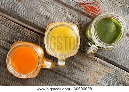 Colorful Trio Of Fresh Fruit Juice In Glass Jugs