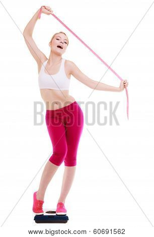 Woman With Measure Tape On Scale Celebrating Weightloss
