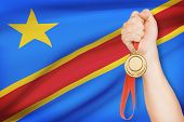 Medal In Hand With Flag On Background - Democratic Republic Of The Congo