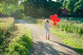 Little Girl With A Bunch Of Red Balloons