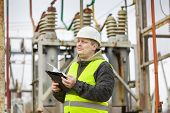 stock photo of substation  - Electrical Engineer with folder in electrical substation - JPG