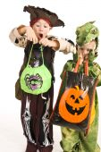 stock photo of happy kids  - Kids in Halloween costumes playing trick or treat and asking for sweets - JPG