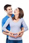 Couple making heart shape on woman belly