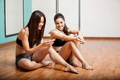 stock photo of pole dancer  - Cute happy pole dancers taking a break from their workout and social networking with a cell phone
