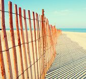 stock photo of wind blown  - Fence on the beach - JPG