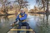 senior canoe paddler in a  canoe on the Cache la Poudre River, Fort Collins, Colorado, winter or ear