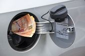 foto of nelson mandela  - concept of south african banknotes feeding into petrol tank indicating petrol price increase - JPG