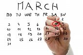 Male Hand Marking On Calendar The Date Of March 8