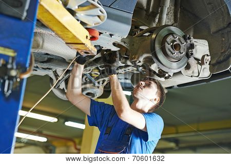 garage auto mechanic repairman checking car suspension during automobile maintenance at repair service station
