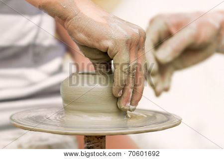 child learning to make a pot on a pottery wheel, old potter helps