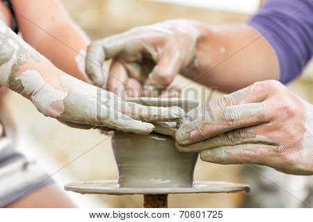 child learning how to make a pot on a pottery wheel, old potter helps