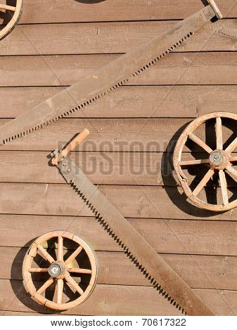 Broken carriage wheels and rusty saws hanging on raw board wall