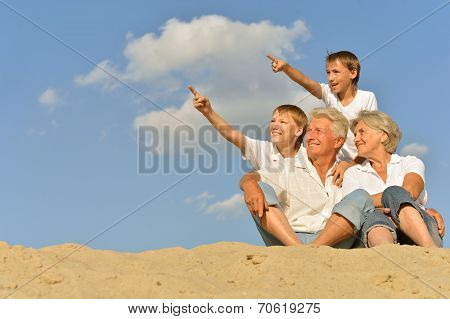 Boys with grandparents sitting on sand