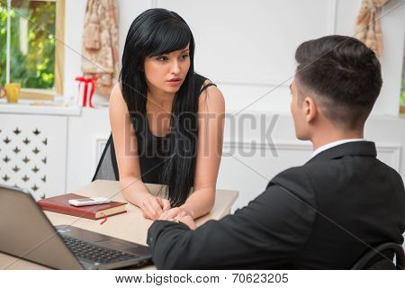 Portrait of young business couple flirting near the table in off