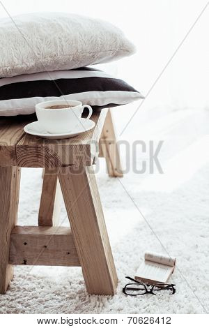 Still life details, stack of black and white cushions on rustic bench on white carpet
