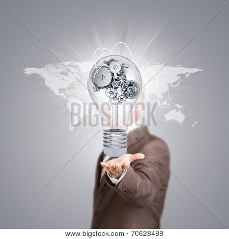 Businessman in a suit hold bulb with metal gears