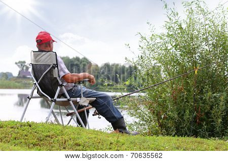 Fisherman Fishes In The River. Middle Aged Man.