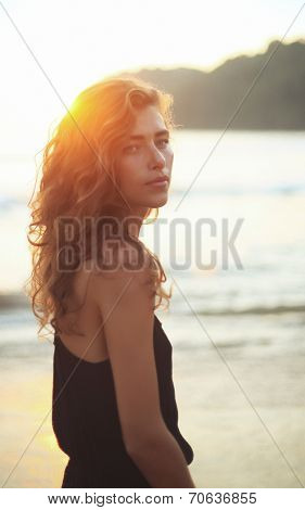 Portrait of a young beautiful woman with long curly hair at the seaside