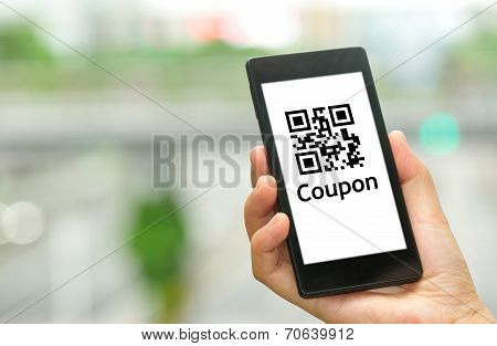 woman hand hold smart phone with coupon QR code in modern city