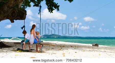 Mother with two kids having fun swinging at tropical beach