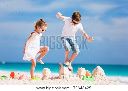 Two kids crushing sandcastle on summer vacation