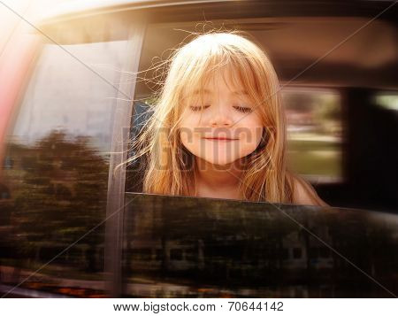 Child Riding In Car Looking Out Window