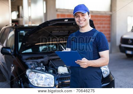 Smiling mechanic writing on a clipboard