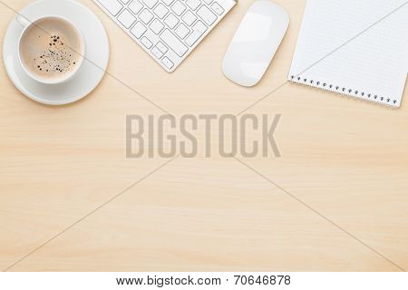 Office table with notepad, computer and coffee cup. View from above with copy space