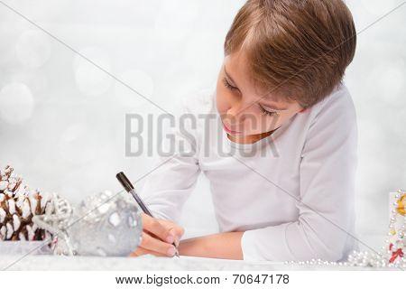 Boy writes a letter to Santa Claus.